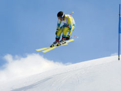 Side view of young male skier at straight downhill race in mid-air