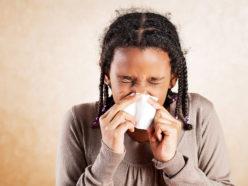 Little girl sneezing in her handkerchief.
